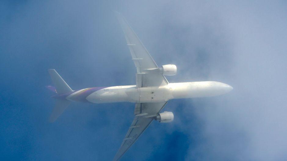 Flugzeug fliegt durch Wolkendecke.