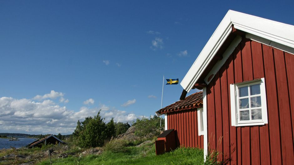 Rote Holzhäuser auf Felsinseln in den Schären vor Västervik in Schweden