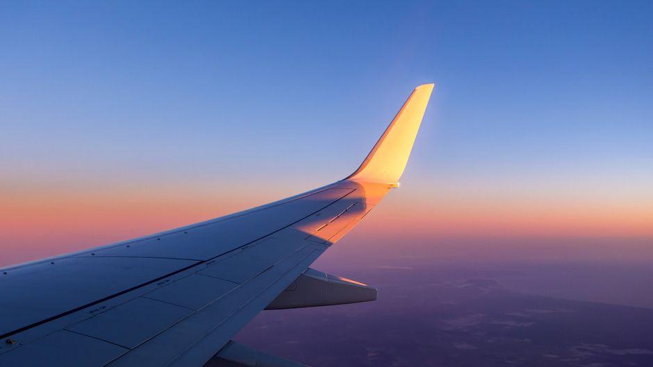 Die Tragfläche eines Flugzeuges ist im Gegenlicht der Sonne kurz nach dem Start in Faro (Algarve in Portugal) zu sehen.