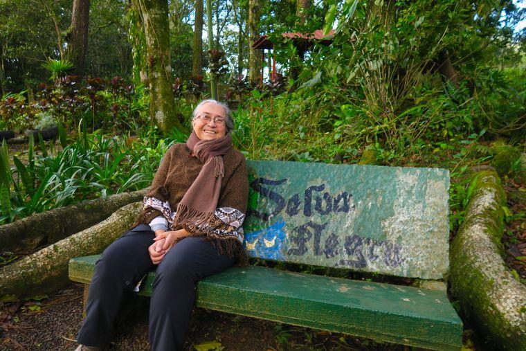 """Mausi Kühl sitzt auf einer Bank auf ihrer Kaffeeplantage """"Selva Negra""""."""
