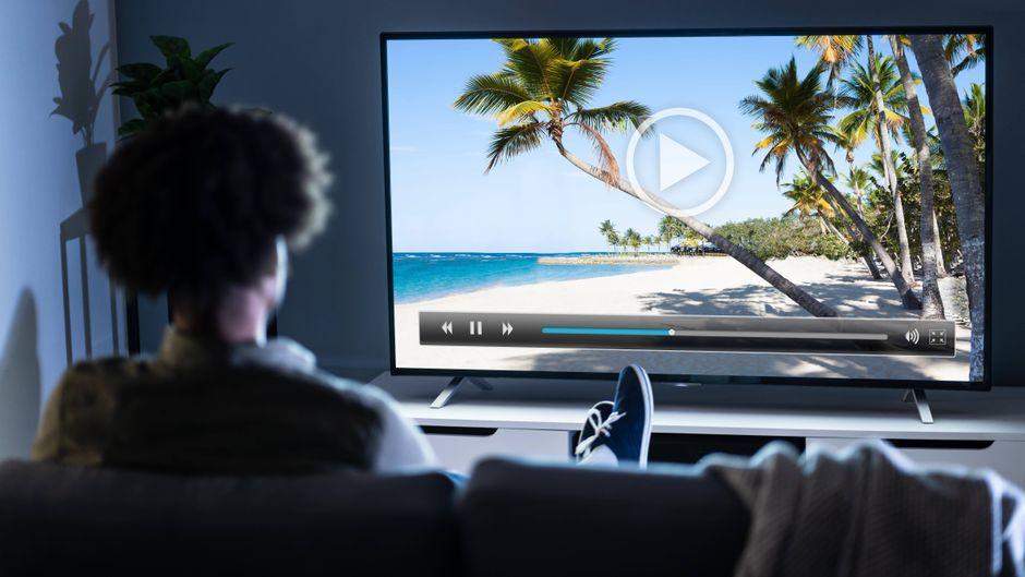 Ein Mann schaut auf den Fernseher mit Strandbild. Mit dem richtigen Film kannst du dich ganz leicht davonträumen.