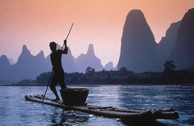Idyllisches Bild in Guilin in China: Ein Paddler im Sonnenuntergang.