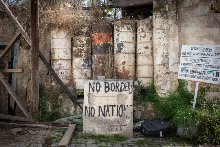 Manchmal stehen Menschen vor Stacheldraht, manchmal vor solchen Barrikaden aus alten Fässern.