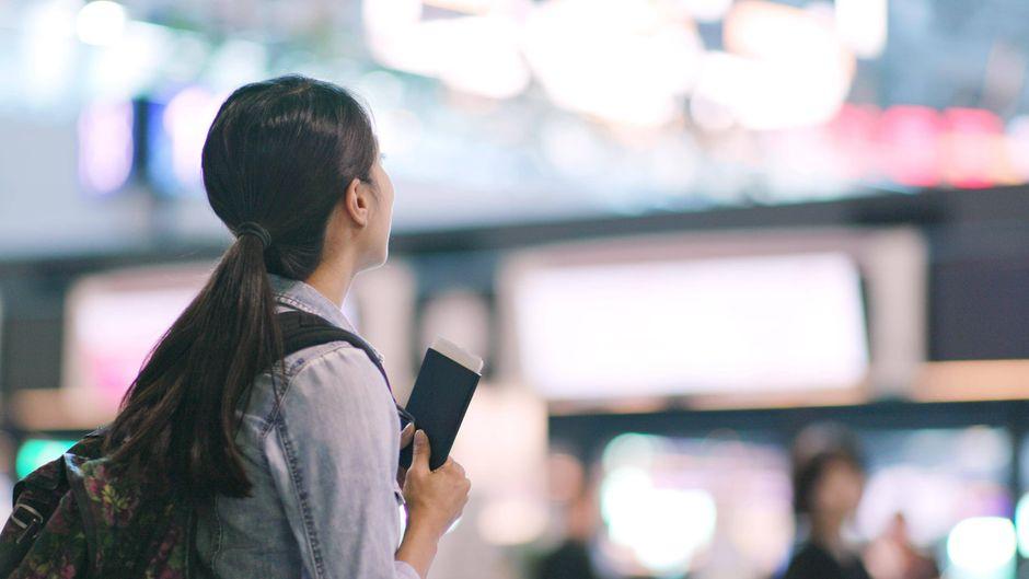 Eine Frau hält ihren Reisepass in der Hand.
