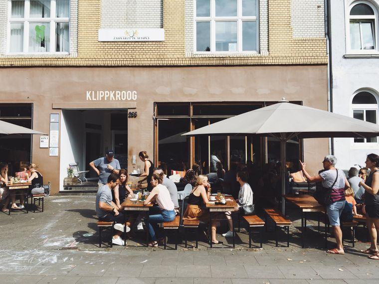 Gäste sitzen auf Bänken vor dem Restaurant Klippkroog mit veganem Angebot in Hamburg.