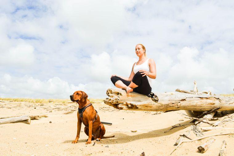 Michelle und Hund Turner beim Yoga am Strand.