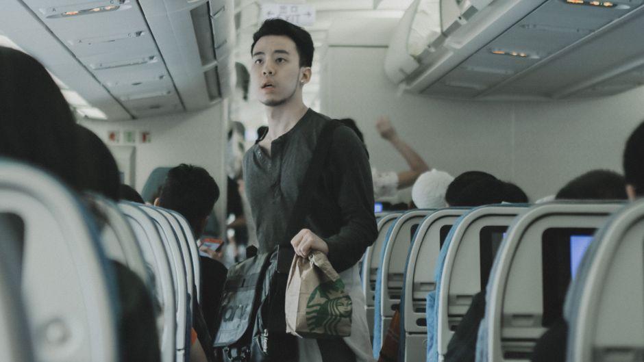 Ein junger Mann geht mit einer Starbucks-Tüte durch die Flugzeugkabine.