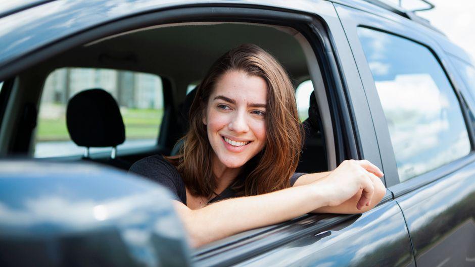Eine Frau blickt aus dem Fenster eines Autos. Bei der Autofahrt in den Urlaub müssen Reisende gewisse Regeln beachten. (Symbolfoto)