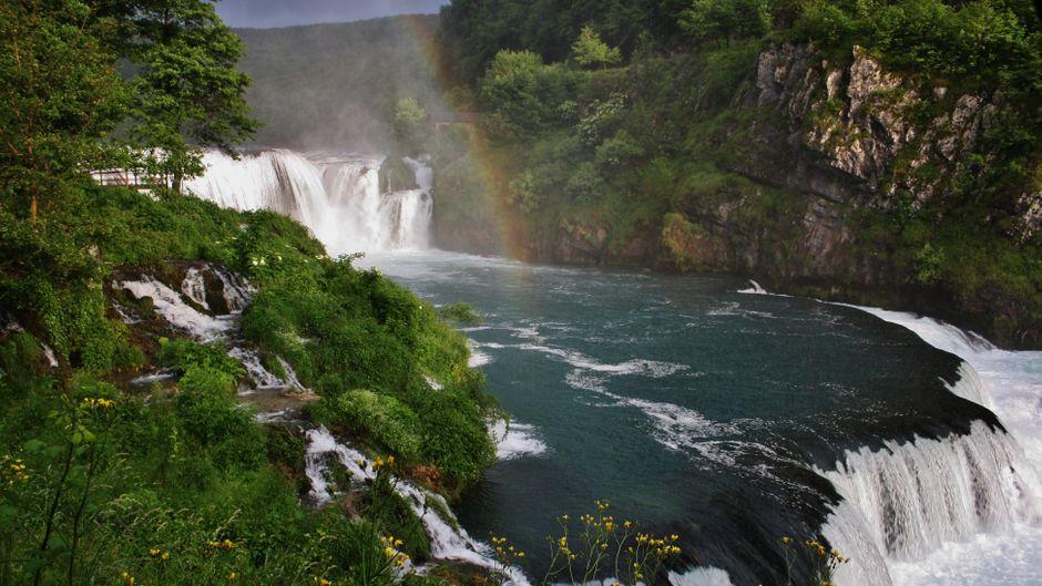 Über einem der zahlreichen Wasserfälle im Nationalpark zeigt sich ein Regenbogen.