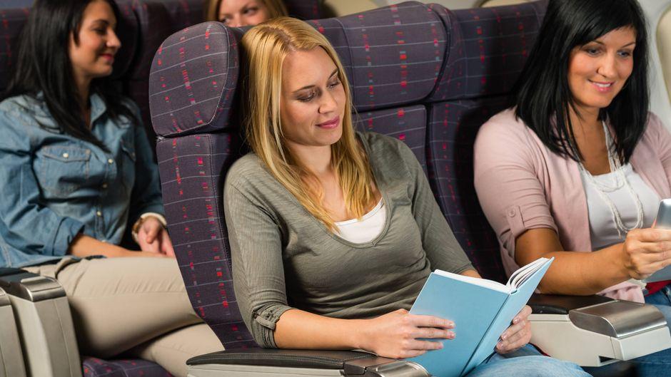 Frau liest im Flugzeug ein Buch.
