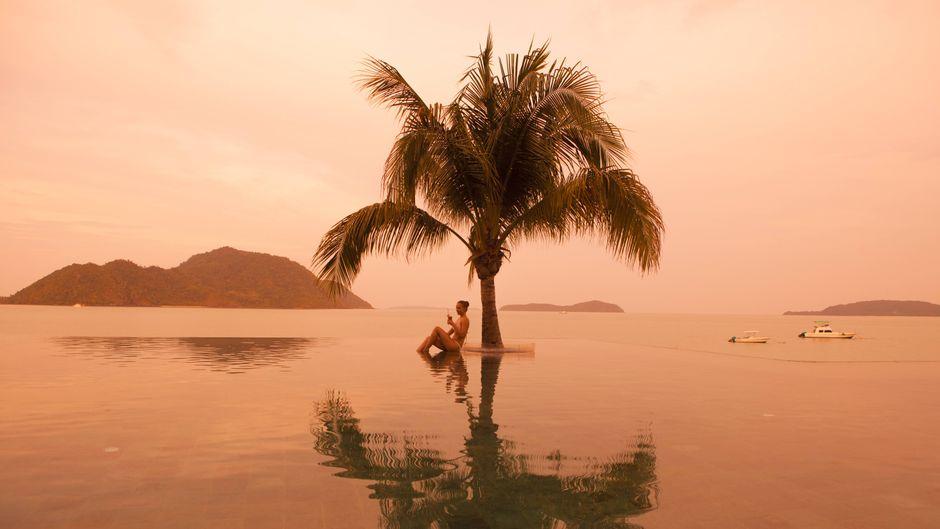 Eine Frau sitzt an einem Pool unter einer Palme in rotem Licht.