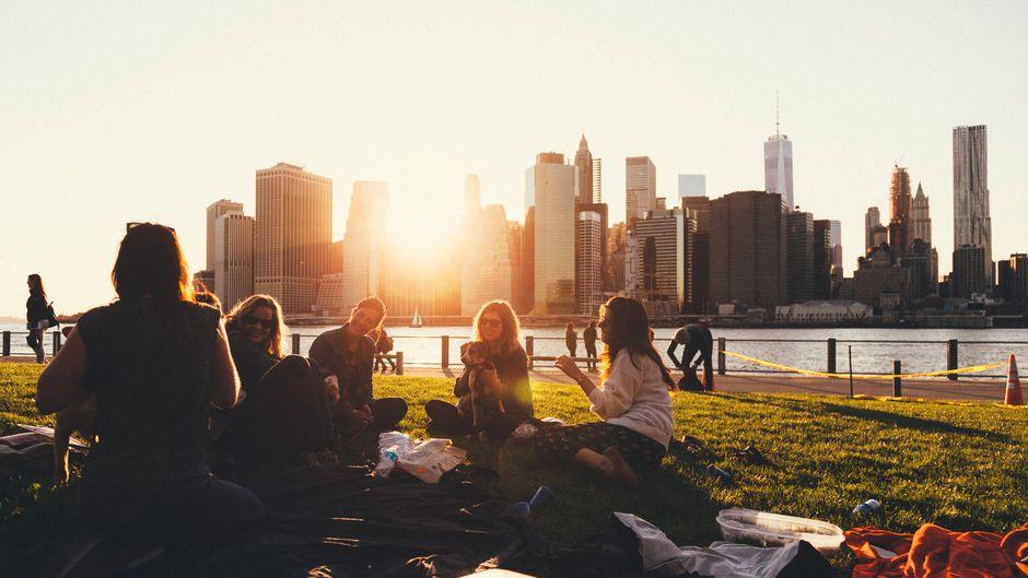 Freunde sitzen im Brooklyn Bridge Park in New York
