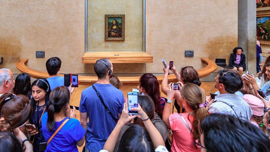 Viele Touristen machen ein Foto von der Mona Lisa im Louvre in Paris.