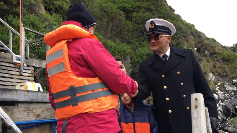 """Der Marineoffizier Victor Arviagada begrüßt den Besuch von der """"Stella Australis"""" mit Handschlag."""