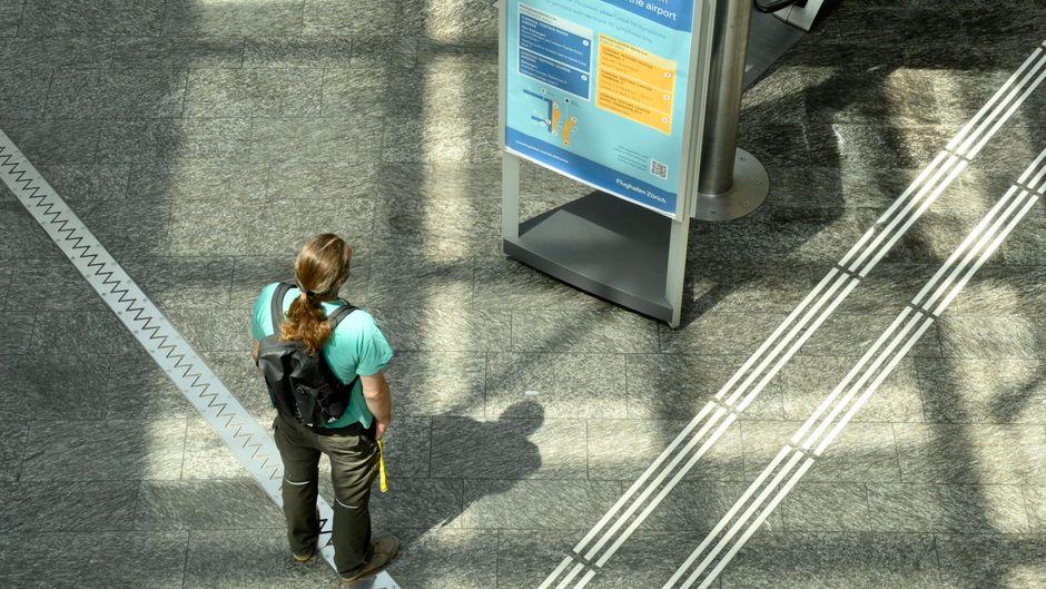 Eine Frau betrachtet ein Infoplakat zum Covid-19-Testcenter am Flughafen Zürich. (Symbolfoto)