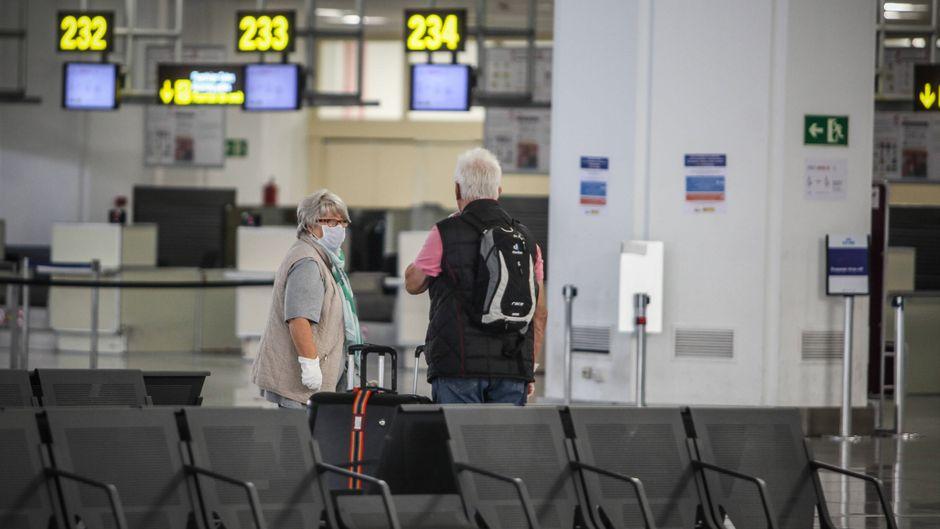 Zwei einsame Fluggäste am Airport von Malaga. Urlaub ist aktuell tabu.