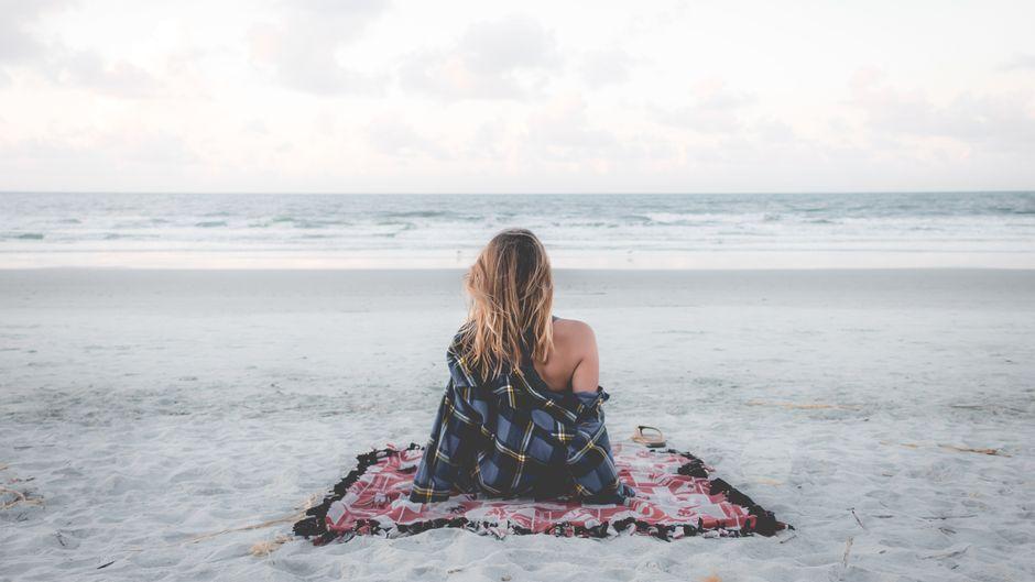 Alleinreisende Frau sitzt im Urlaub am Strand.