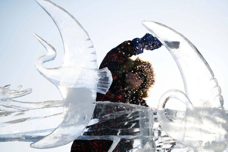 Ein Künstler meißelt eine Skulptur mit Vögeln aus Eis.