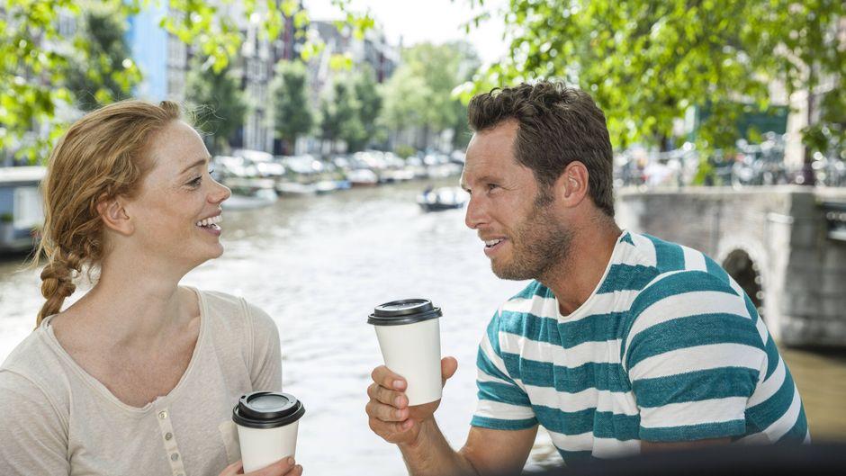 Ein Mann und eine Frau trinken an einer Gracht in Amsterdam Kaffee.