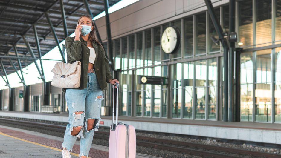 Frau am Flughafen – mit Mund-Nasen-Bedeckung und Koffer.