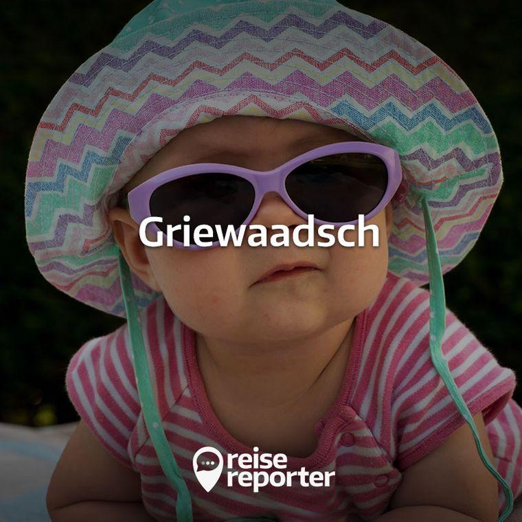 Ein Baby mit Sonnenhut und Sonnenbrille.