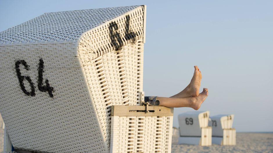 Mensch im Strandkorb auf Sylt an der Nordsee streckt seine Füße aus dem Strandkorb