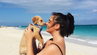 Urlauberin kuschelt am Strand der Turks- und Caicosinseln mit einem Welpen.