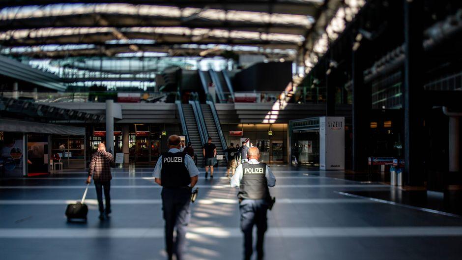Der Flughafen Dresden Mitte Juli: Blick in die leere Ankunftshalle mit zwei Beamten der Bundespolizei bei einem Kontrollrundgang.