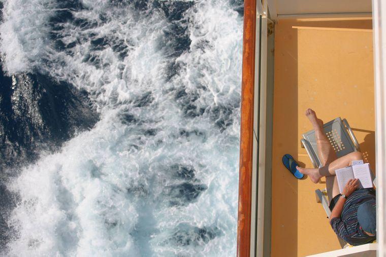 Ein Mann sitzt auf einem Balkon auf einem Kreuzfahrtschiff.