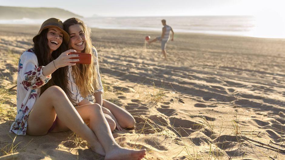Zwei Freundinnen fotografieren sich am Strand