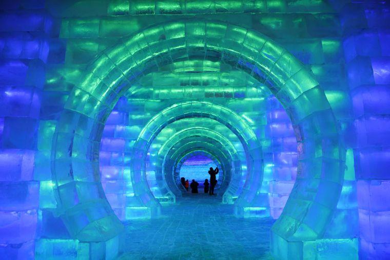 Ein blau und grün beleuchteter Tunnel komplett aus Eis.