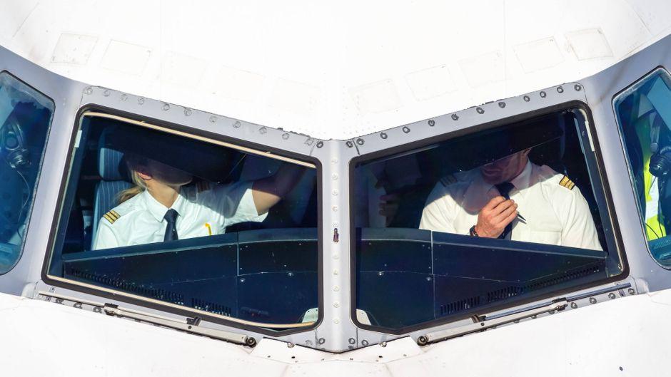 Zwei Piloten sitzen im Cockpit eines Flugzeuges.