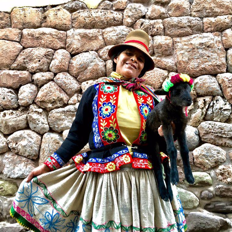 Eine Frau in Anden-Tracht mit einem schwarzen Baby-Alpaka im Arm.