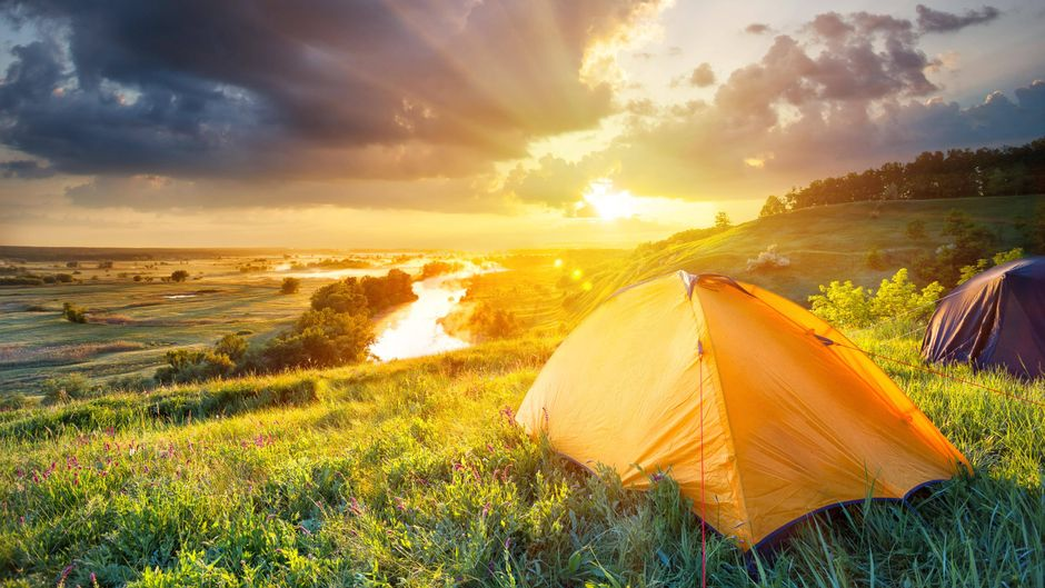 Orangefarbenes Zelt im Sonnenuntergang am Meer.