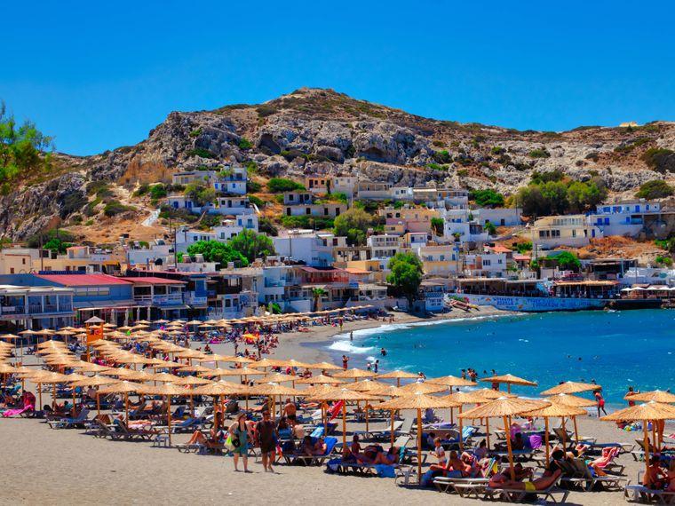 Urlauber entspannen am Strand von Matala auf der griechischen Insel Kreta.