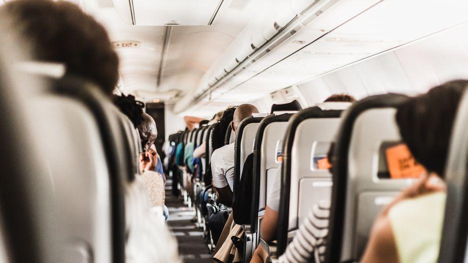 Passagiere sitzen in einem Flugzeug.