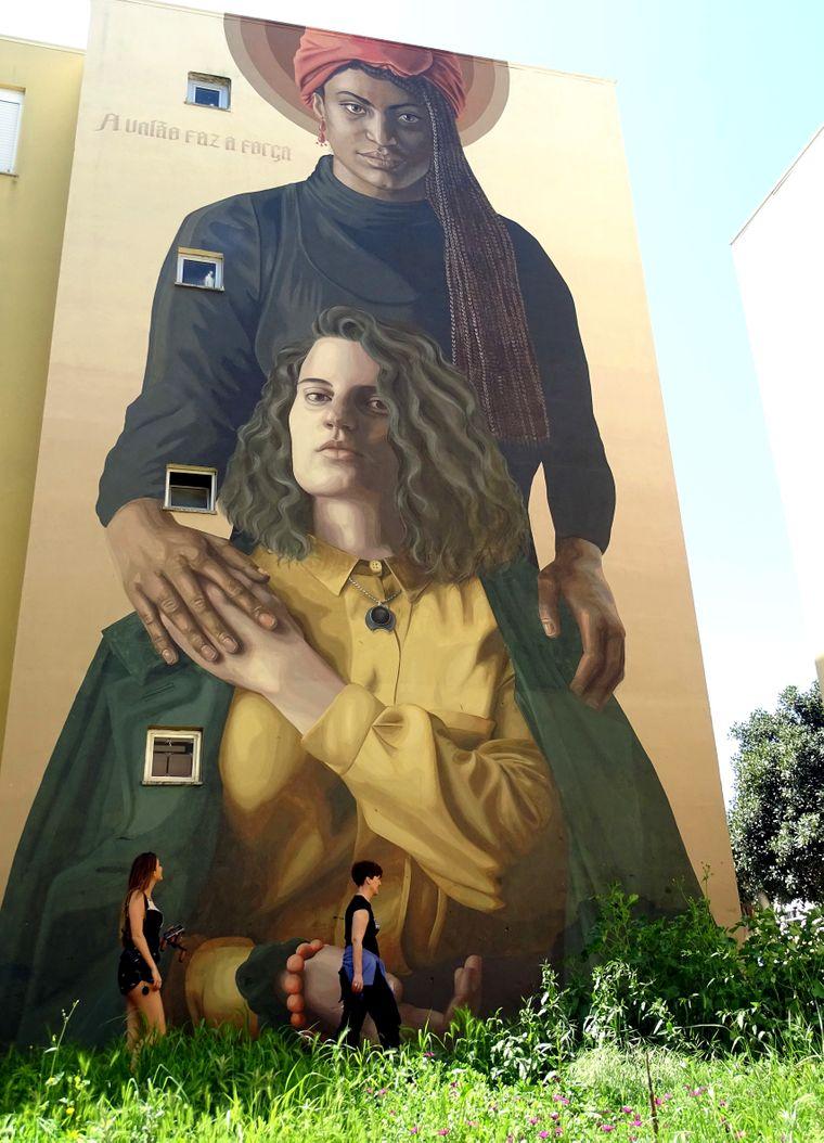 """Bis zu zwölf Meter hoch sind die Kunstwerke an den Fassaden und Hauswänden in Lissabon. In der Vorstadt Sacavém soll es etwa 70 dieser Riesenformate geben. """"Unity creates strength"""" heißt das Gemeinschaftswerk von Camilo Núñez und Florencia Durán."""