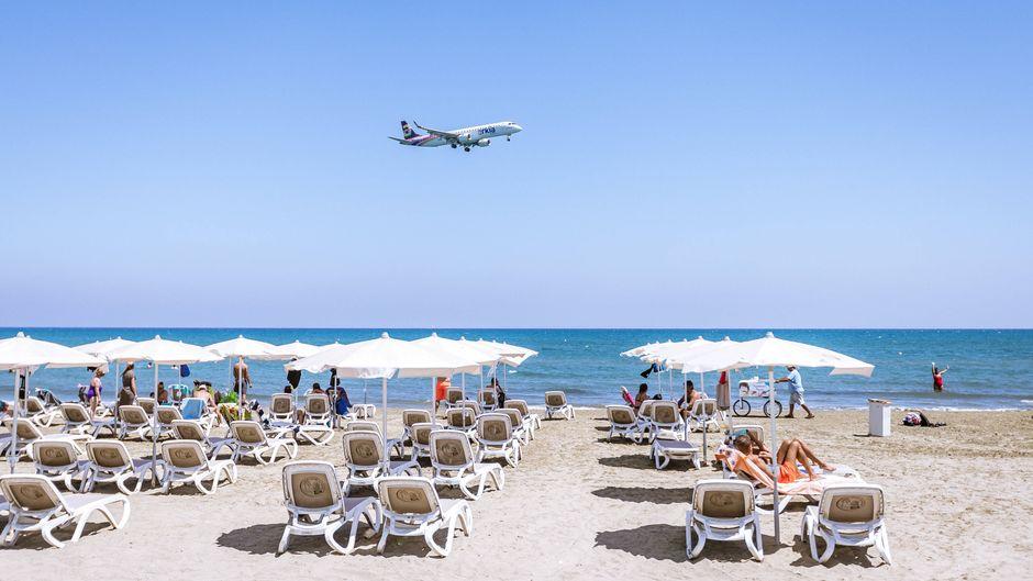 Ein Flugzeug beim Landeanflug über Touristinnen und Touristen mit Sonnenliegen und Sonnenschirmen. (Symbolbild)