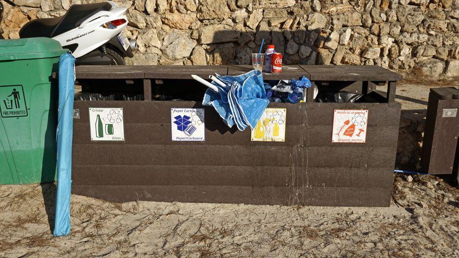 Die Abfallbehälter am Strand Cala Mondrago, Mallorca, Balearen, quellen fast über.