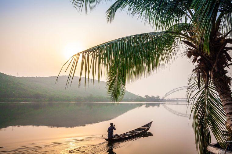 Einheimischer paddelt in einem Holzkanu auf dem Volta-Fluss in der gleichnamigen Region in Ghana.