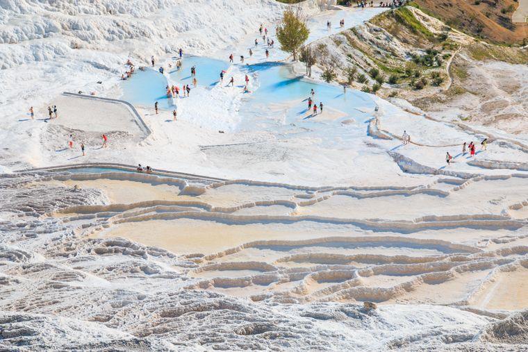 Blick auf Touristen, die zwischen der Salzterrasse von Pamukkale spazieren.