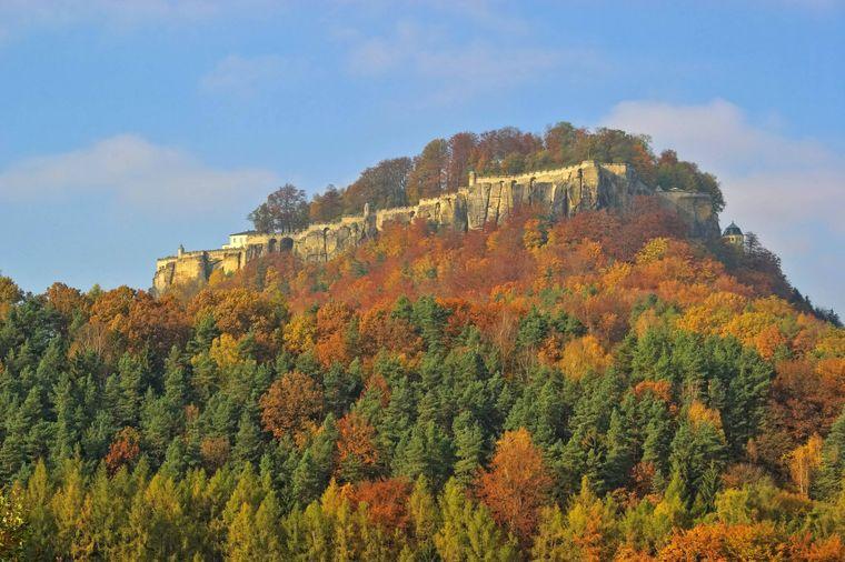 Die Festung Königstein im Elbsandsteingebirge – eingebettet in buntes Herbstlaub.