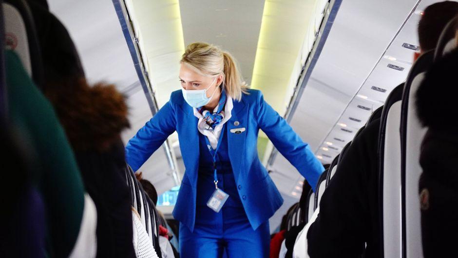 Eine Flugbegleiterin geht während der Corona-Pandemie in einer Flugzeugkabine mit Mund-Nasen-Schutz durch die Sitzreihen. Bei einem Flug gibt es gute und schlechte Passagiere. Eine Flugbegleiterin spricht über ihre Lieblingsgäste. Foto: imago images/Frank Sorge