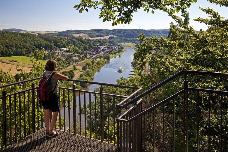 Eine Frau blickt vom Skywalk auf die Weser – ein tolles Ausflugsziel in der Region.