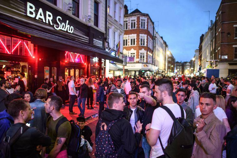 Menschen feiern vor einem Pub im Soho-Viertel in London