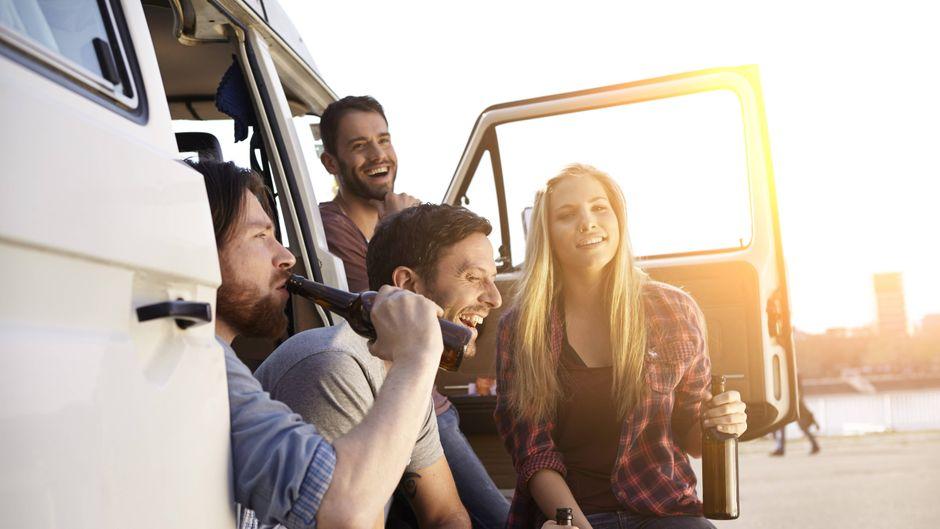 Freunde trinken Bier im Minivan