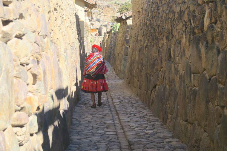 Eine Frau läuft durch die Gassen der Anden-Stadt Ollantaytambo in Peru.