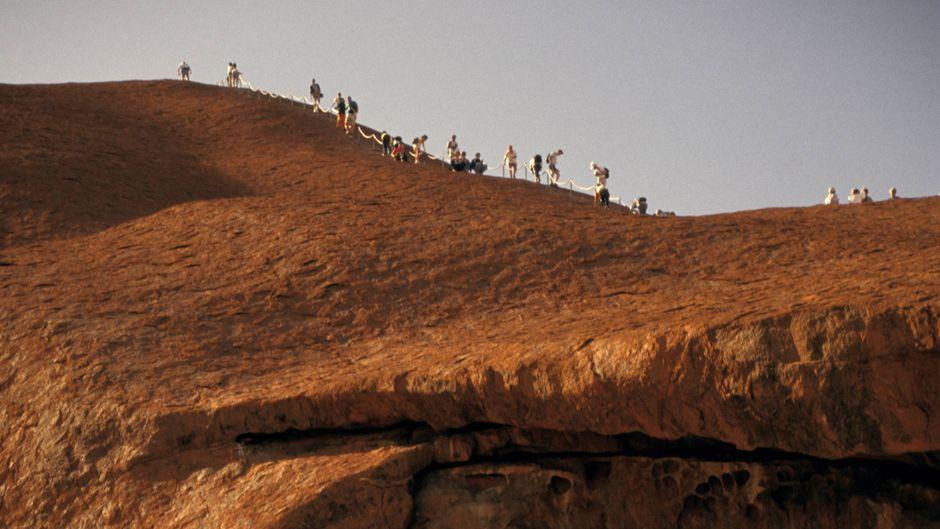 Touristen klettern auf den Gipfel des Uluru (Ayers Rock) in Australien.