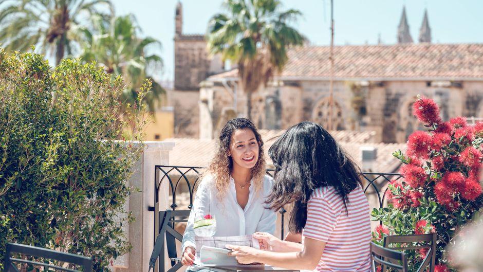 Zwei Frauen sitzen in einem Café auf Mallorca – mit Blick auf die Kathedrale von Palma. Urlaub in Spanien ist im Sommer 2021 möglich.
