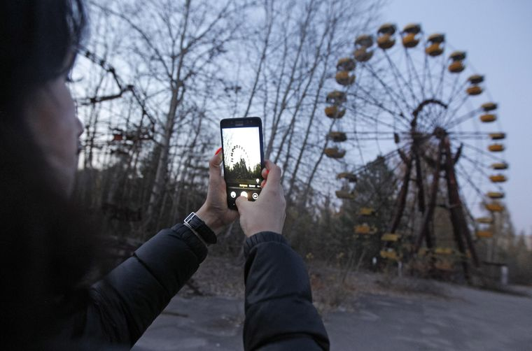 Besucherin fotografiert ein Riesenrad im verlassenen Freitzeitpark von Pripyat.